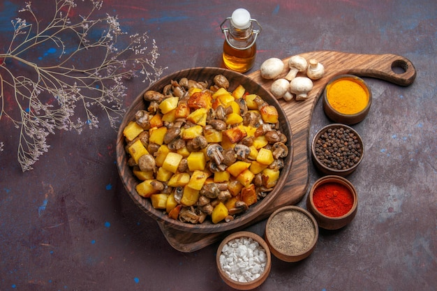 Top-nahansicht-teller mit speiseteller mit kartoffeln und champignons, champignonöl in der flasche und bunten gewürzen