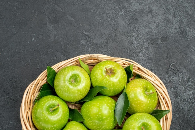 Top nahaufnahme äpfel im korb brauner korb der grünen äpfel mit blättern