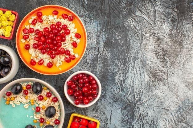 Top nahaufnahme ansicht beeren trauben kirschen rote johannisbeeren bonbons haferflocken mit granatapfelkernen