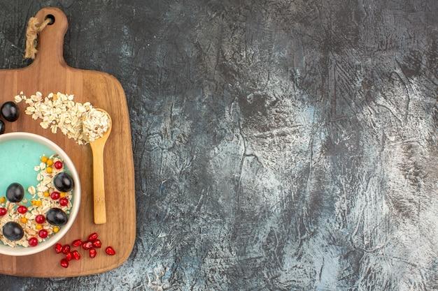 Top nahaufnahme ansicht beeren trauben samen von granatapfel haferflocken löffel auf dem brett