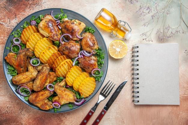 Top nahaufnahme ansicht huhn hühnerflügel kartoffeln kräuter zwiebeln öl zitronengabel messer weißes notizbuch