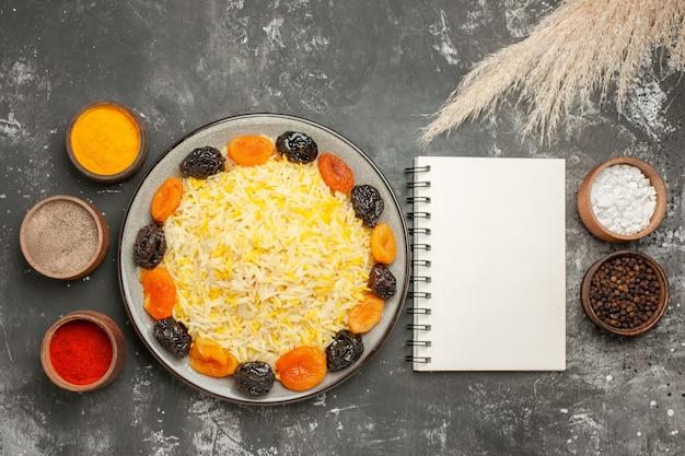 Top nahaufnahme ansicht reisplatte reis mit getrockneten früchten notebook gewürze