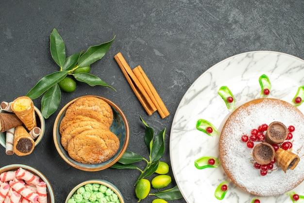 Top nahaufnahme ansicht süßigkeiten kuchen mit beeren süßigkeiten zimt zitrusfrüchte waffeln kekse