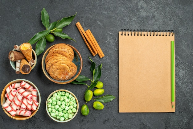 Top nahaufnahme ansicht süßigkeiten süßigkeiten zimt zitrusfrüchte waffeln kekse notizbuch bleistift