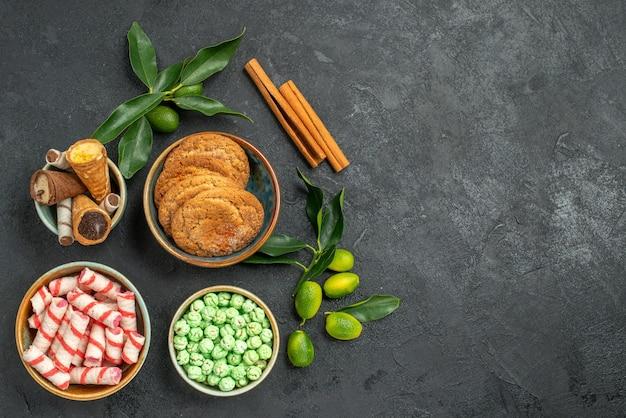 Top nahaufnahme ansicht süßigkeiten waffeln kekse bunte süßigkeiten zimtstangen zitrusfrüchte mit blättern