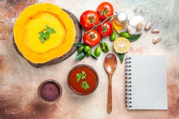 Top nahaufnahme ansicht suppenlöffel tomaten knoblauch zitronenöl kürbissuppe sauce weißes notizbuch