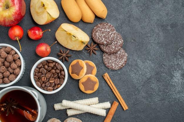 Top nahaufnahme ansicht tee eine tasse tee kekse nüsse kaffeebohnen äpfel kirschen
