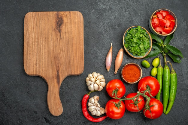 Top nahaufnahme ansicht tomaten zwiebeln knoblauch gewürze kräuter peperoni tomaten das schneidebrett