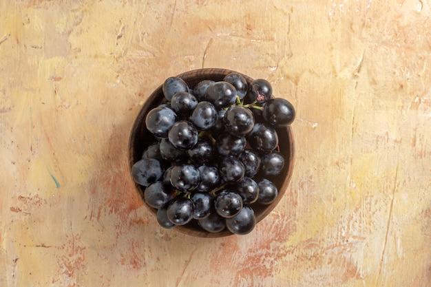 Top nahaufnahme ansicht trauben schüssel trauben von schwarzen trauben auf dem cremetisch