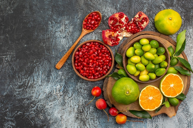 Top-nahaufnahme ansicht zitrusfrüchte schüssel granatapfelkernen löffel zitrusfrüchte auf dem brett