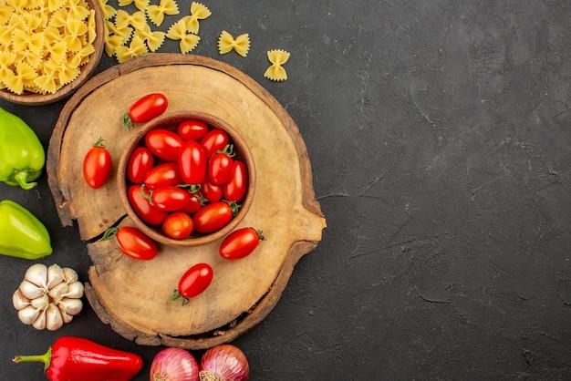 Top nahaufnahme appetitanregendes gemüse schneidebrett mit einer schüssel tomaten und appetitlichem gemüse auf dem schwarzen tisch