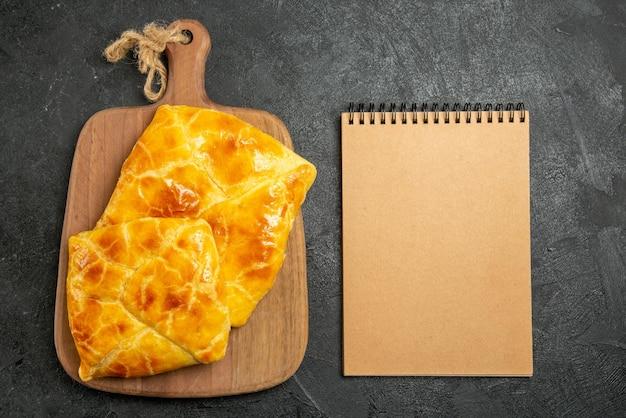 Top-nahaufnahme appetitanregendes kuchen-creme-notizbuch neben den appetitlichen kuchen auf dem schneidebrett auf dem dunklen tisch