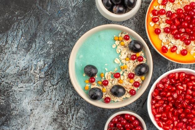 Top nahaufnahme beeren die appetitlichen haferflocken rote johannisbeeren trauben granatäpfel