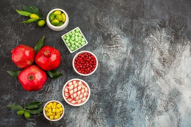Top nahaufnahme bonbons die appetitlichen grün-weiß-gelben bonbons limetten und drei granatäpfel