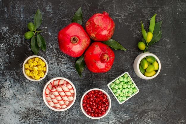 Top nahaufnahme bonbons drei granatäpfel die appetitlichen grünen weißen gelben bonbons limetten