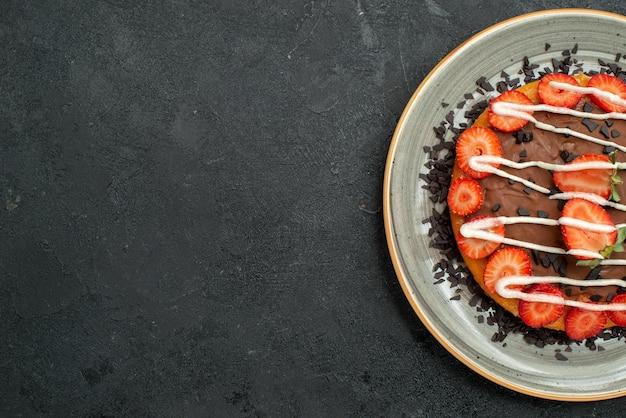 Top nahaufnahme dessert appetitlicher kuchen mit erdbeerstücken und schokolade auf weißem teller auf der rechten seite des dunklen tisches