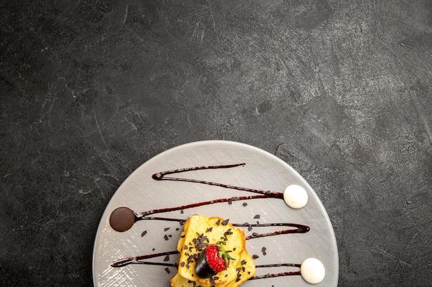 Top nahaufnahme dessertkuchen mit schokoladenüberzogenen erdbeeren und schokoladensauce auf dem schwarzen tisch