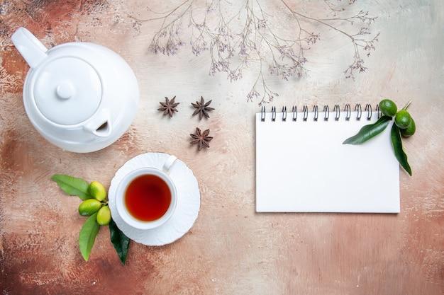 Top-nahaufnahme eine tasse tee eine tasse tee weiße teekanne zitrusfrüchte sternanis notizbuch