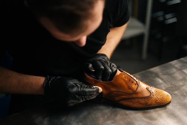 Top-nahaufnahme eines professionellen schusters mit schwarzen handschuhen, der alte hellbraune lederschuhe poliert?