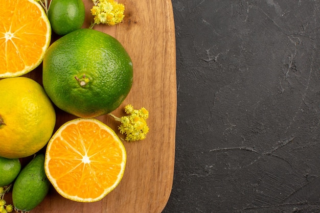 Top nahaufnahme frische mandarinen mit feijoa auf dunklem raum dark