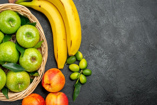 Top nahaufnahme früchte bananen limetten äpfel im korb und nektarinen auf dem tisch