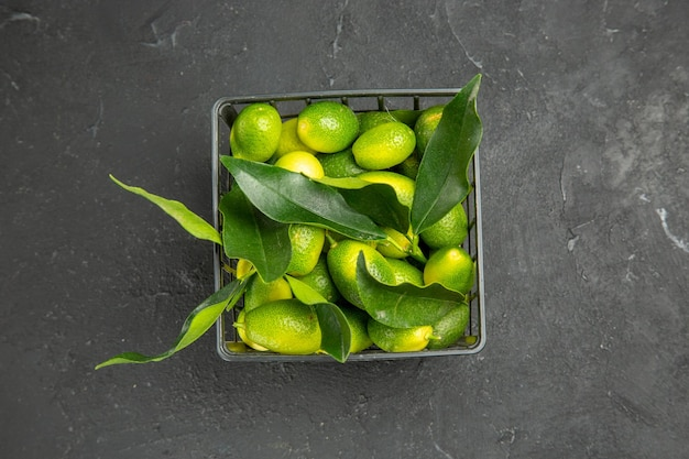 Top nahaufnahme früchte früchte mit blättern im dunklen korb