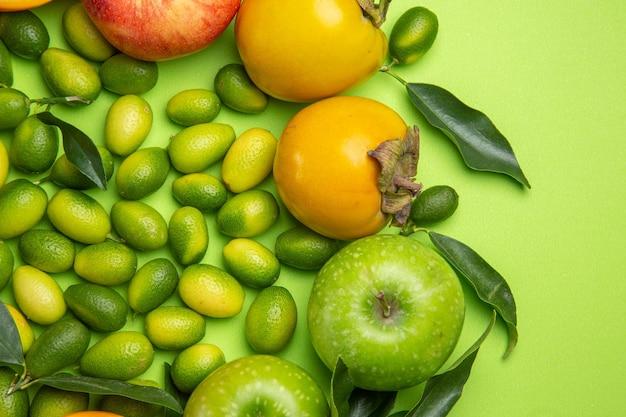 Top nahaufnahme früchte zitrusfrüchte äpfel kaki auf dem tisch