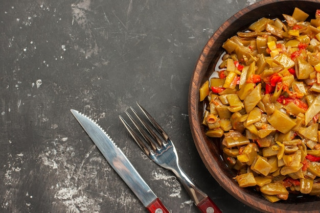 Top-nahaufnahme-gericht auf der tischplatte der appetitlichen grünen bohnen und tomaten neben der gabel und dem messer auf dem dunklen tisch