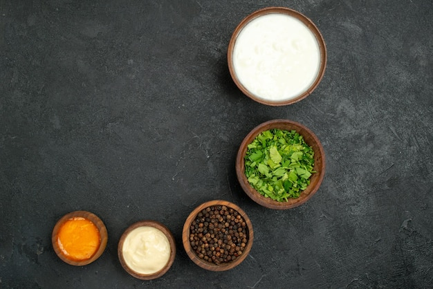 Top nahaufnahme gewürze und saucen schalen mit gelben und weißen saucen sauerrahm schwarzer pfeffer und kräuter auf dunkler oberfläche