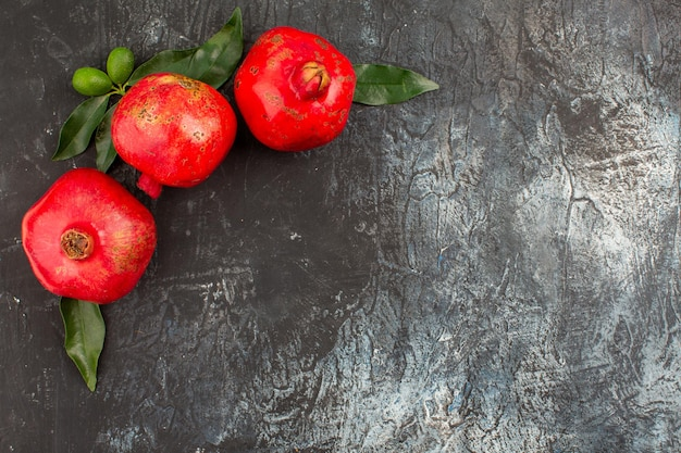 Top nahaufnahme granatäpfel drei appetitliche granatäpfel mit grünen blättern