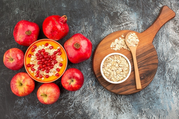 Top-nahaufnahme granatäpfel haferflocken äpfel granatäpfel haferflocken und löffel auf dem brett