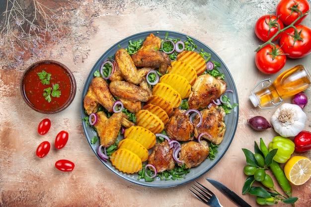 Top nahaufnahme huhn hühnerflügel kartoffeln zwiebel kräuter gemüse sauce gabel messer