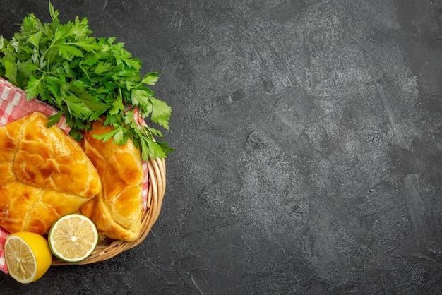 Top nahaufnahme käsekräuter schüsseln mit kräutern und käse und korb mit appetitlichen kuchen zitronenkräuter und karierte tischdecke auf dem tisch