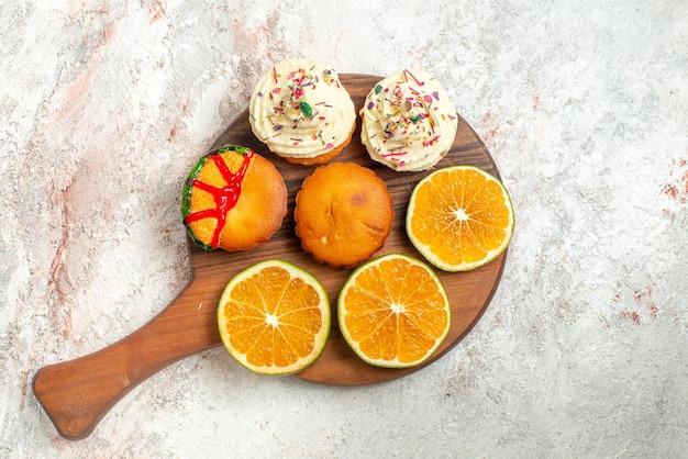 Top nahaufnahme kekse appetitliche kekse und zitrusfrüchte auf dem schneidebrett auf der hellen oberfläche
