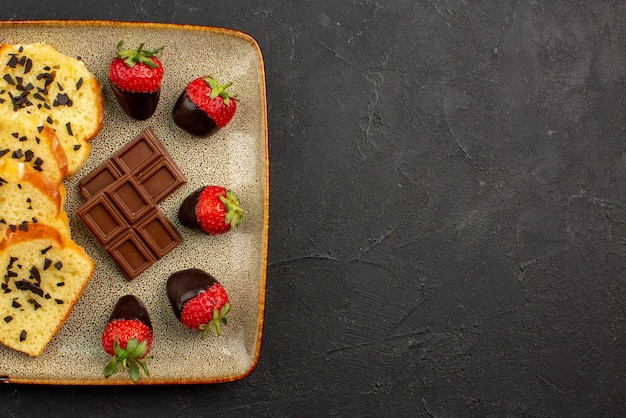Top nahaufnahme kuchen auf teller kuchen mit schokolade und schokoladenüberzogenen erdbeeren auf dem quadratischen grauen teller auf der linken seite des tisches