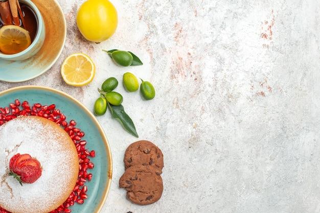 Top nahaufnahme kuchen blauer kuchenteller mit erdbeerplätzchen zitrusfrüchte auf dem tisch