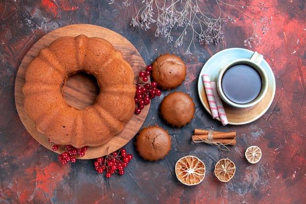Top nahaufnahme kuchen eine tasse tee kuchen mit roten johannisbeeren auf dem brett cupcakes zitrone zimt