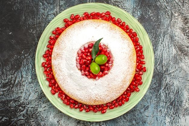 Top-nahaufnahme-kuchen mit beeren der kuchen mit granatapfel-zitrusfrüchten auf dem weißen teller