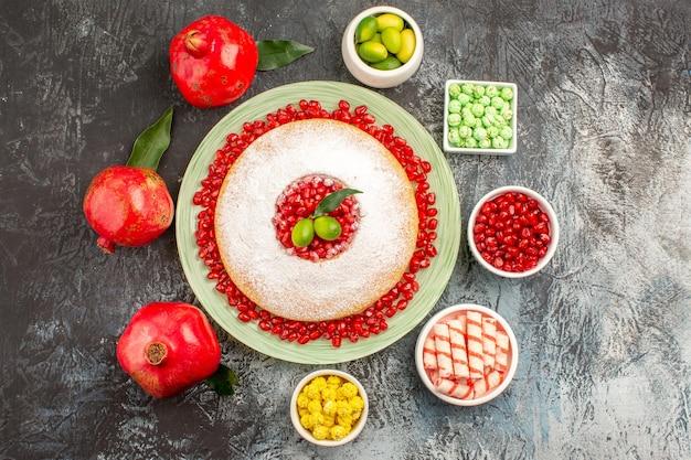 Top nahaufnahme kuchen süßigkeiten granatapfel der teller mit kuchen zitrusfrüchte granatäpfel bonbons