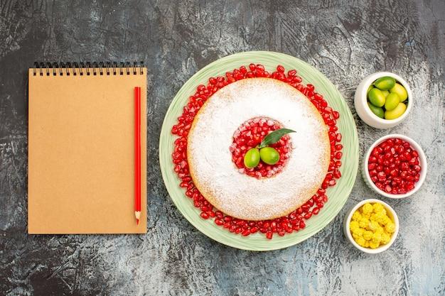 Top nahaufnahme kuchen und süßigkeiten ein appetitlicher kuchen zitrusfrüchte bonbons notizbuch rotstift