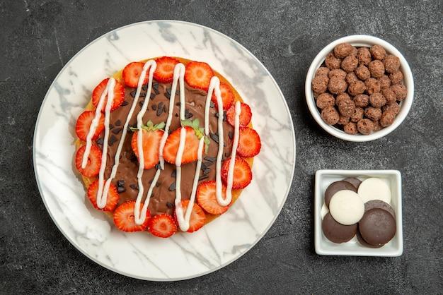 Top nahaufnahme kuchen und süßigkeiten schalen mit haselnüssen und schokolade und kuchen mit schokolade und erdbeeren