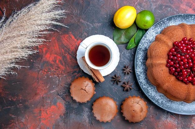 Top nahaufnahme kuchen weizenähren kuchen zitrusfrüchte cupcakes eine tasse tee mit zimt