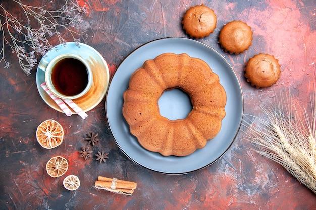 Top nahaufnahme leckerer kuchen leckerer kuchen eine tasse schwarzer tee zitrone sternanis süßigkeiten drei cupcakes