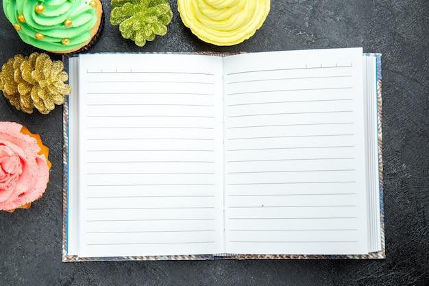 Top nahaufnahme mini bunte cupcakes und ein notizbuch auf dunklem hintergrund