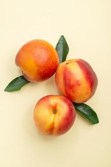 Top nahaufnahme nektarine drei nektarinen mit blättern auf der weißen oberfläche
