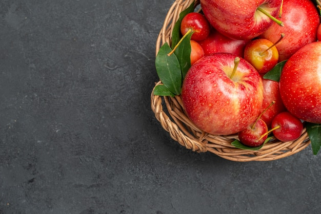 Top nahaufnahme obst äpfel und beeren im korb auf dem dunklen tisch