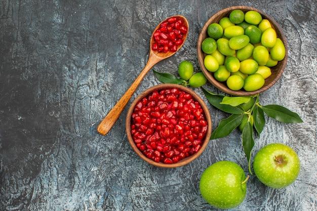Top nahaufnahme obst äpfel und zitrusfrüchte in der schüssel samen von granatäpfeln