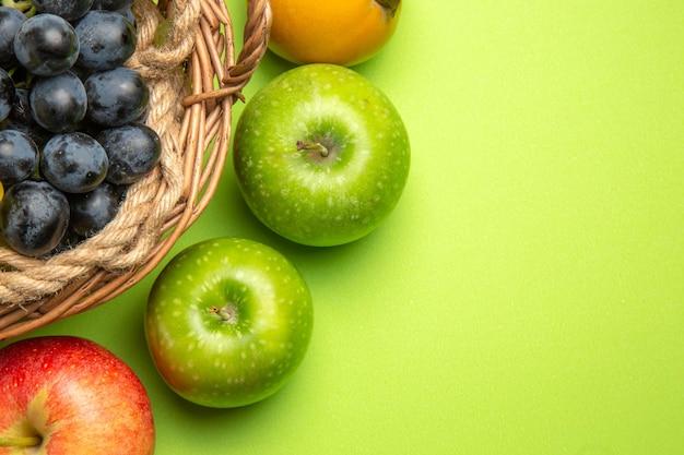Top nahaufnahme obstkorb mit schwarzen trauben kaki äpfel