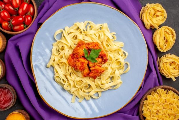 Top nahaufnahme pasta und saucen schüsseln mit tomaten und verschiedene arten von saucen neben dem teller mit nudelfleisch und soße auf der lila tischdecke