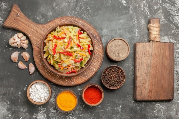 Top nahaufnahme salat knoblauch schalen mit bunten gewürzen gemüsesalat auf dem schneidebrett